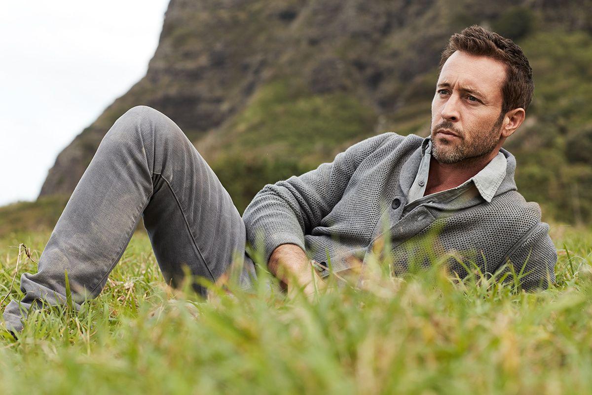 Alex O\u2019Loughlin laying in grass wearing gray sweater