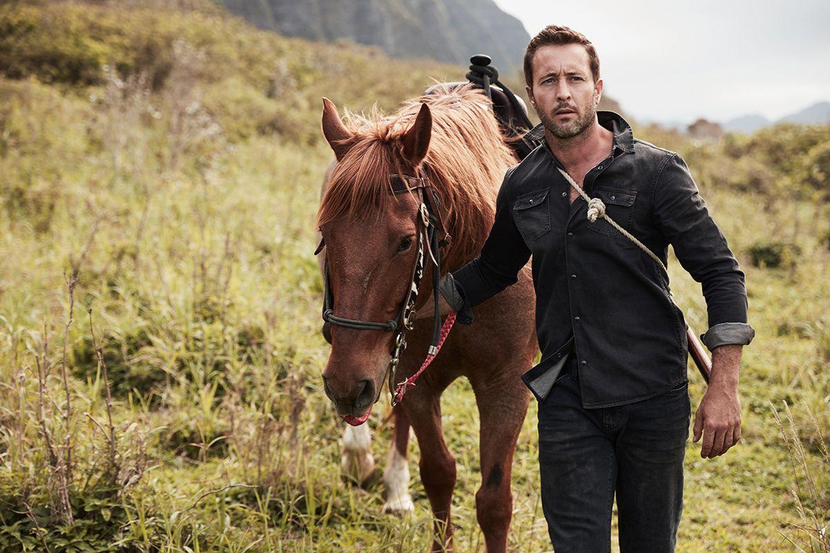 Alex O'Loughlin walking with a brown horse