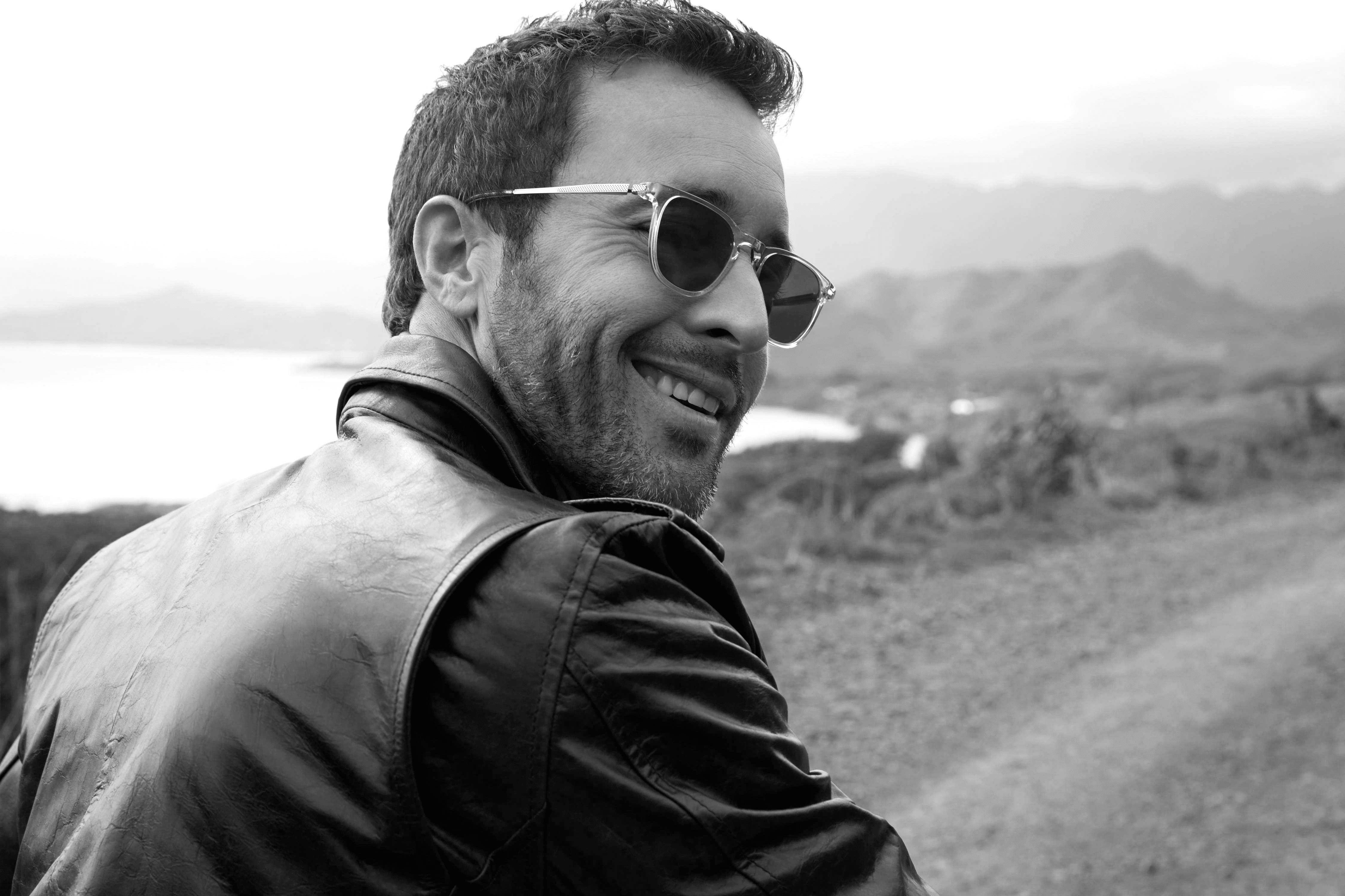 Alex O'Loughlin smiling wearing sunglasses