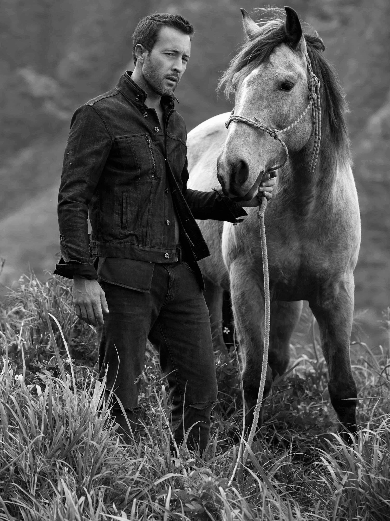 Black and white of Alex O'Loughlin posing with a horse
