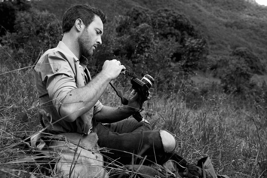 Black and white photo of Alex O\u2019Loughlin holding a camera