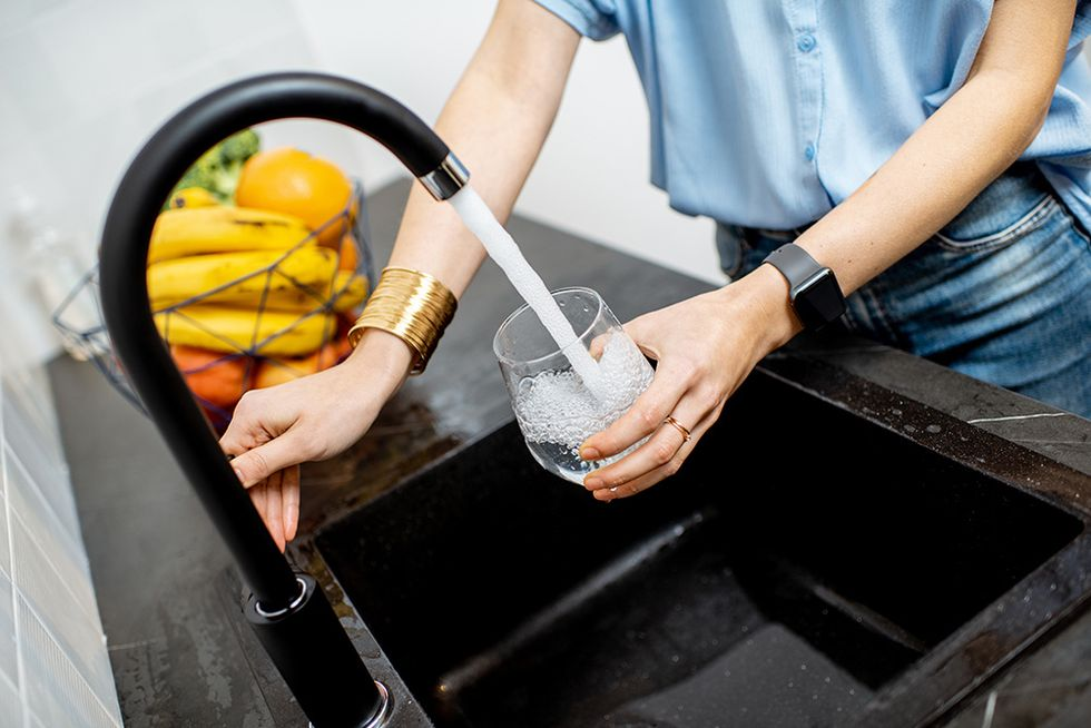A woman fills up a glass cup with water at a sleek black sink. A bowl of fruit sits beside the sink.