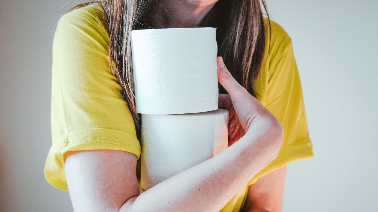 woman holding rolls of toilet paper