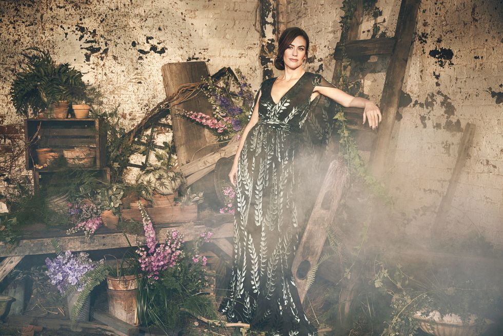 Maggie Siff in a floral dress among floral arrangements.
