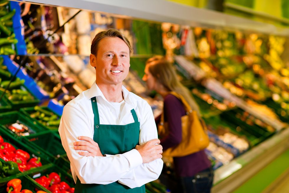 A grocery store associate stocks the produce section.