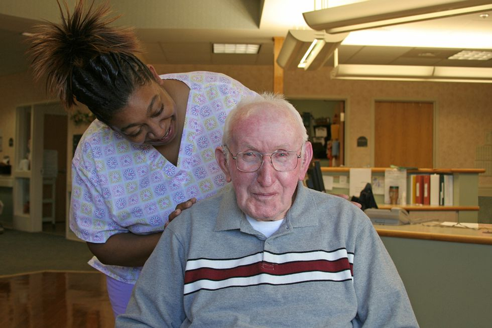 A health care worker checks on a patient.