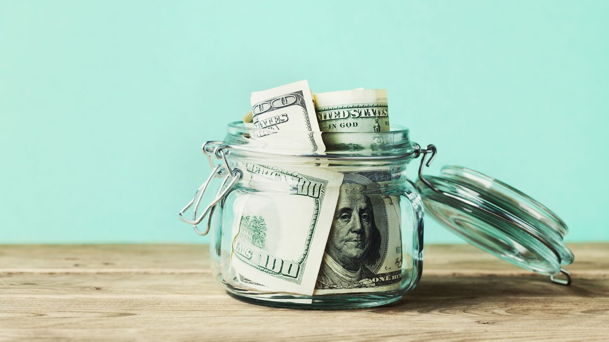 money personalities concept of saving money dollar bills in glass jar against blue background