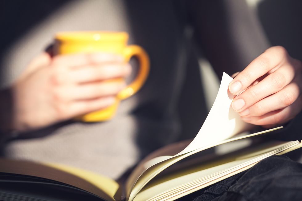 Close up of a woman's hands holding an open book and a yellow mug.