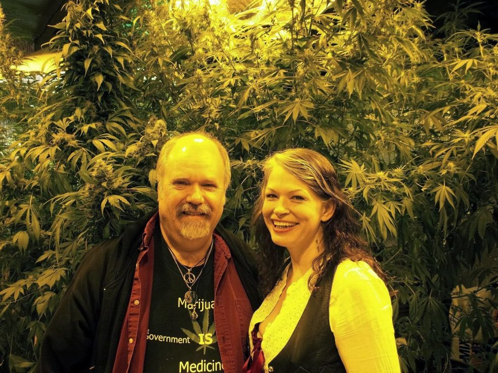A smiling man and woman in front of a large cannabis bush