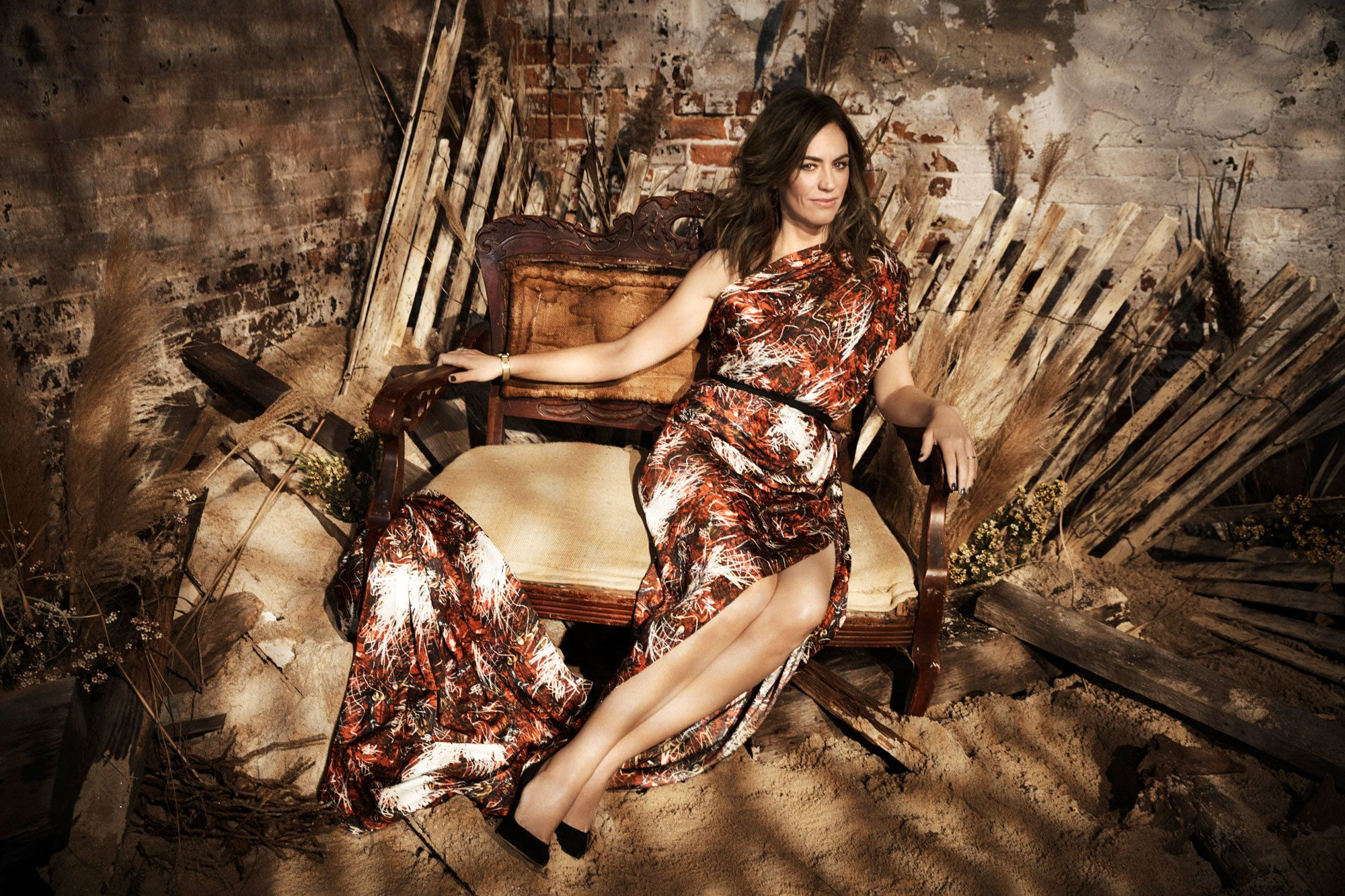Maggie Siff sitting on a shabby-chic chair that looks like a throne.