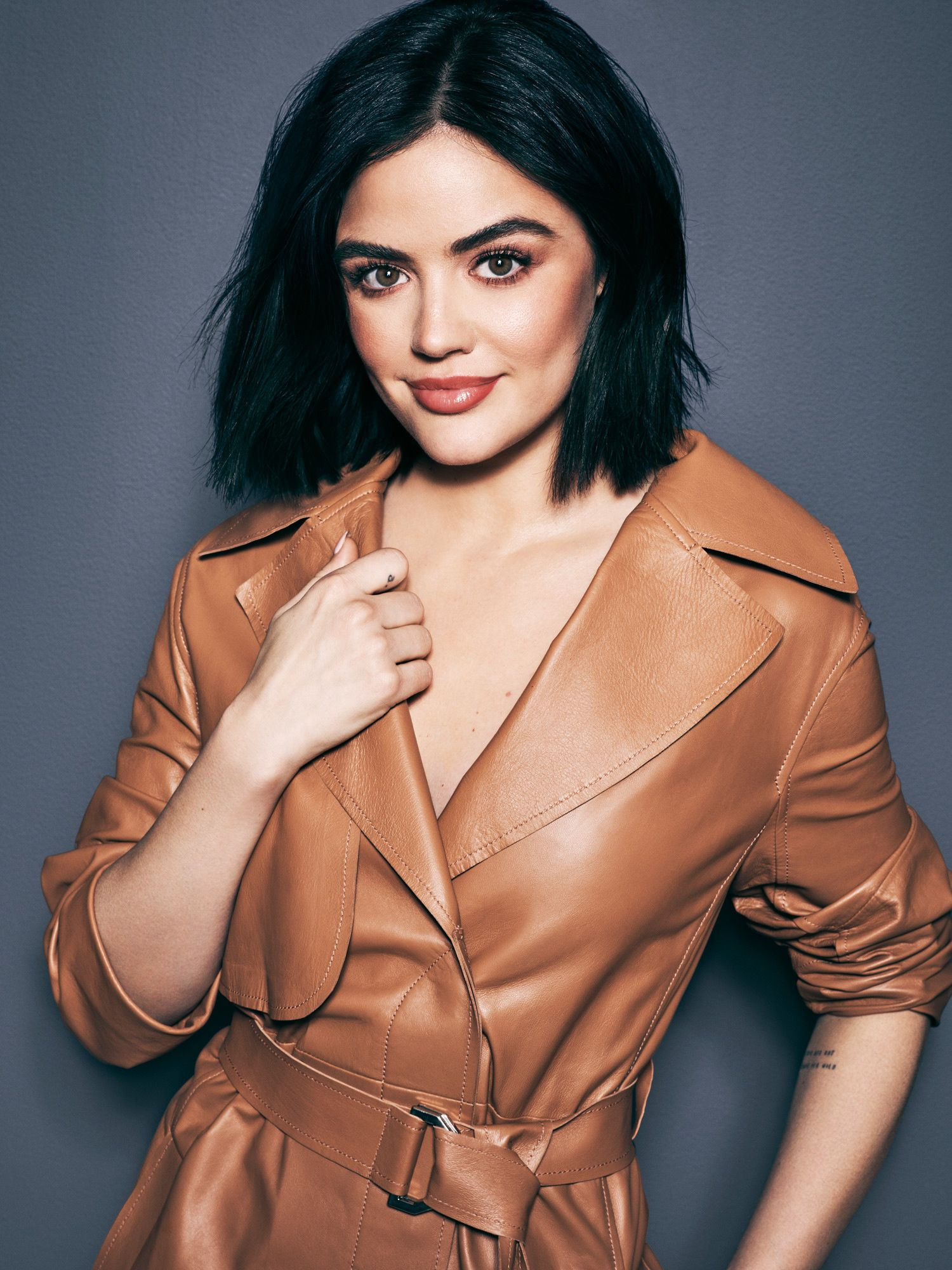 Lucy Hale in a brown leather trench coat.