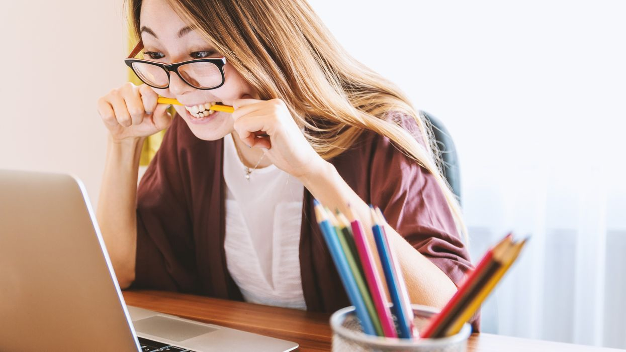 stressed out woman biting on pencil staring at her computer