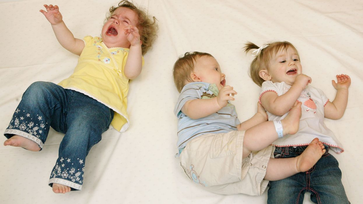 Toddlers lying down smiling, playing and crying