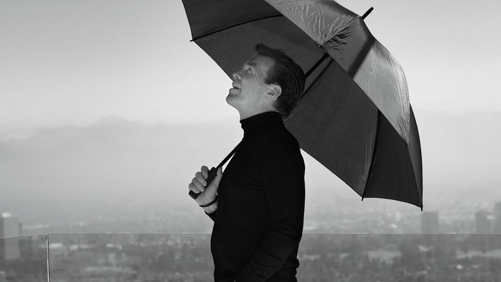 A black and white of Peter Bergman under an umbrella and staring up at the sky