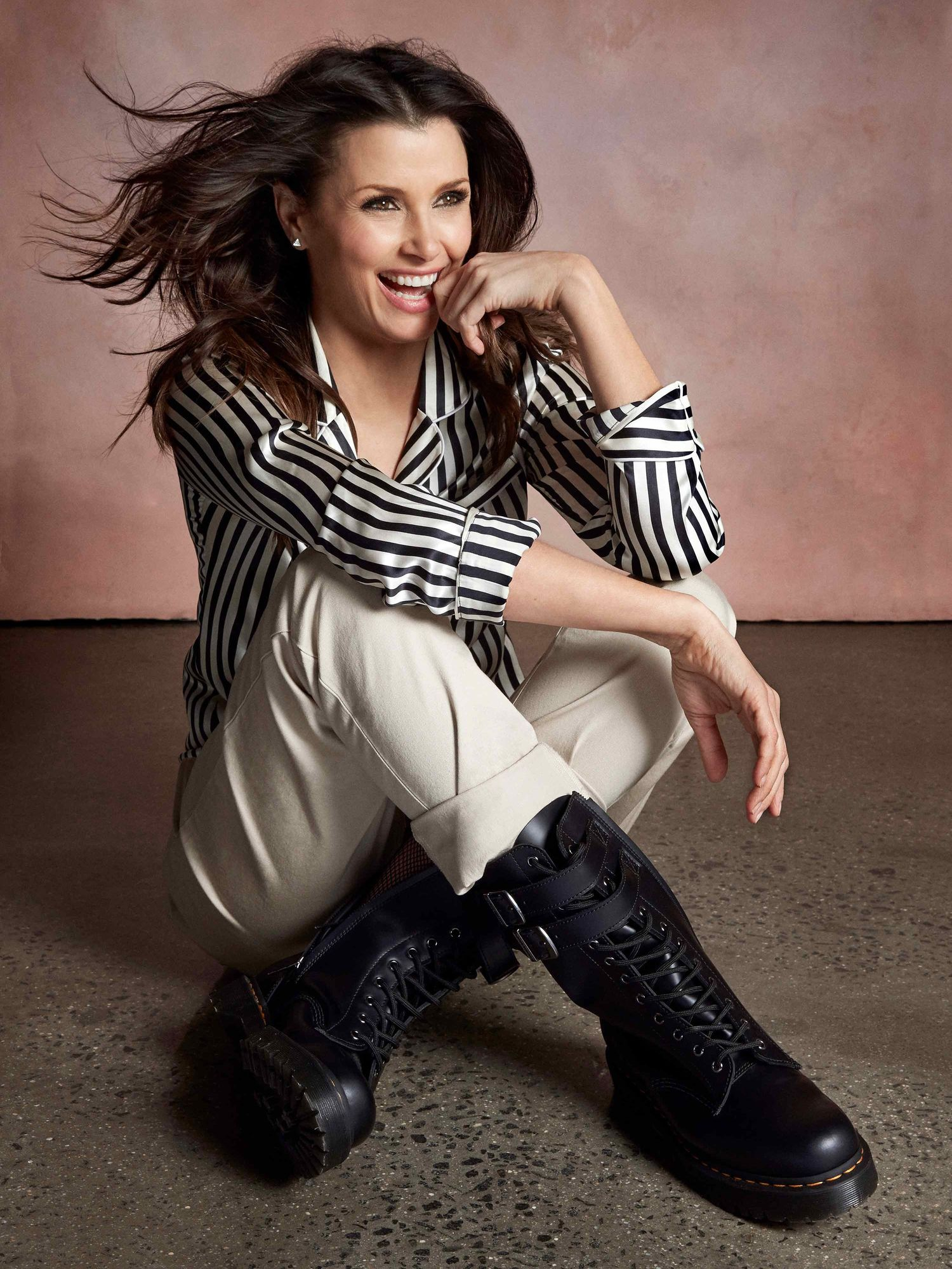 Bridget Moynahan sitting wearing striped shirt and black leather boots
