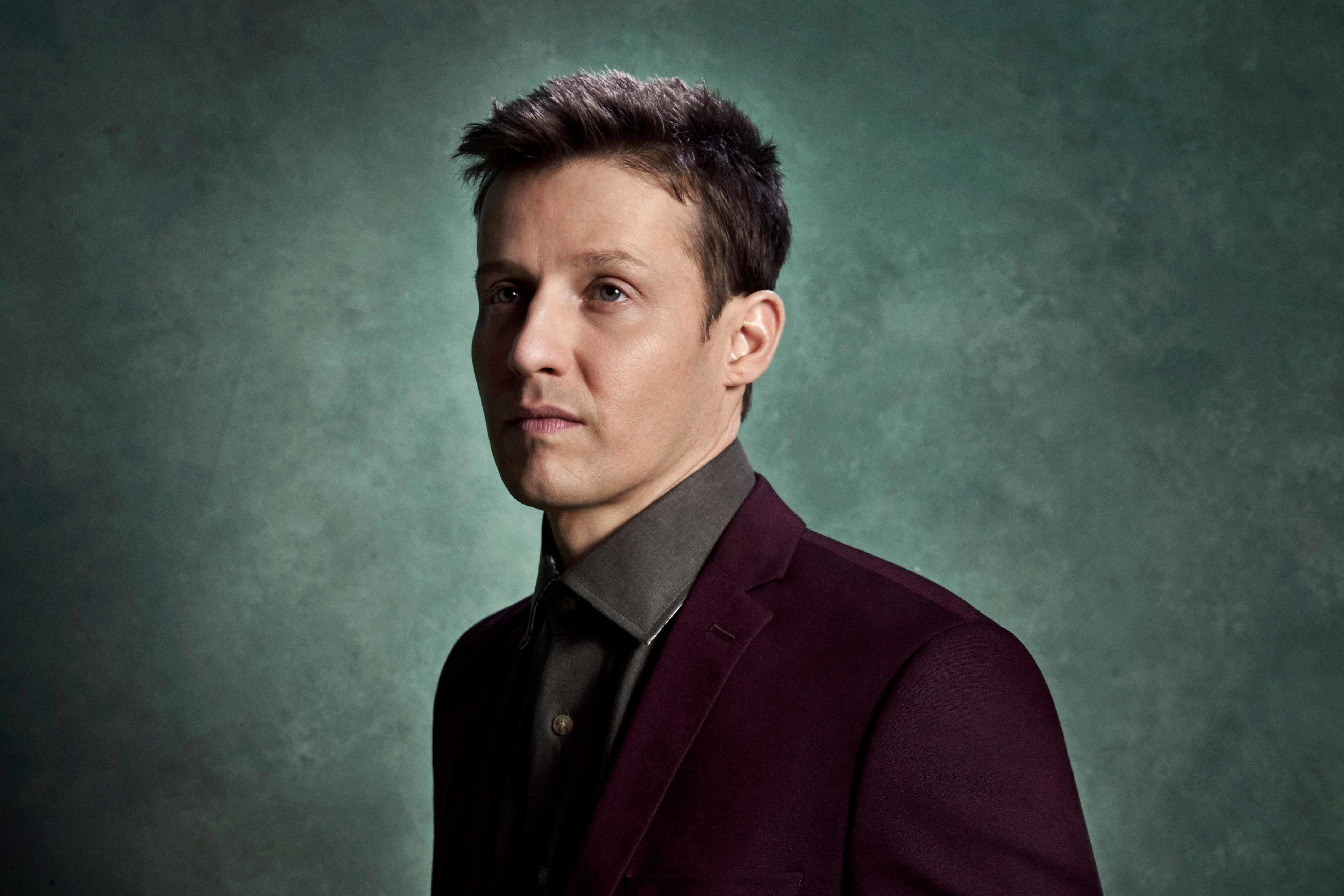 Will Estes wearing a burgundy blazer