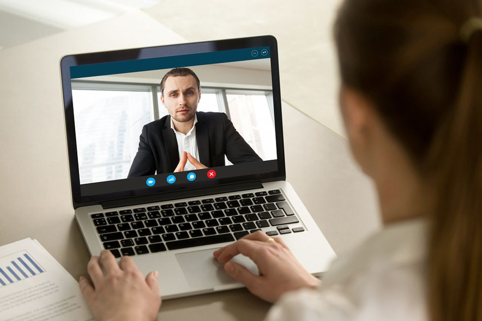 A business manager holds a video meeting with an employee.