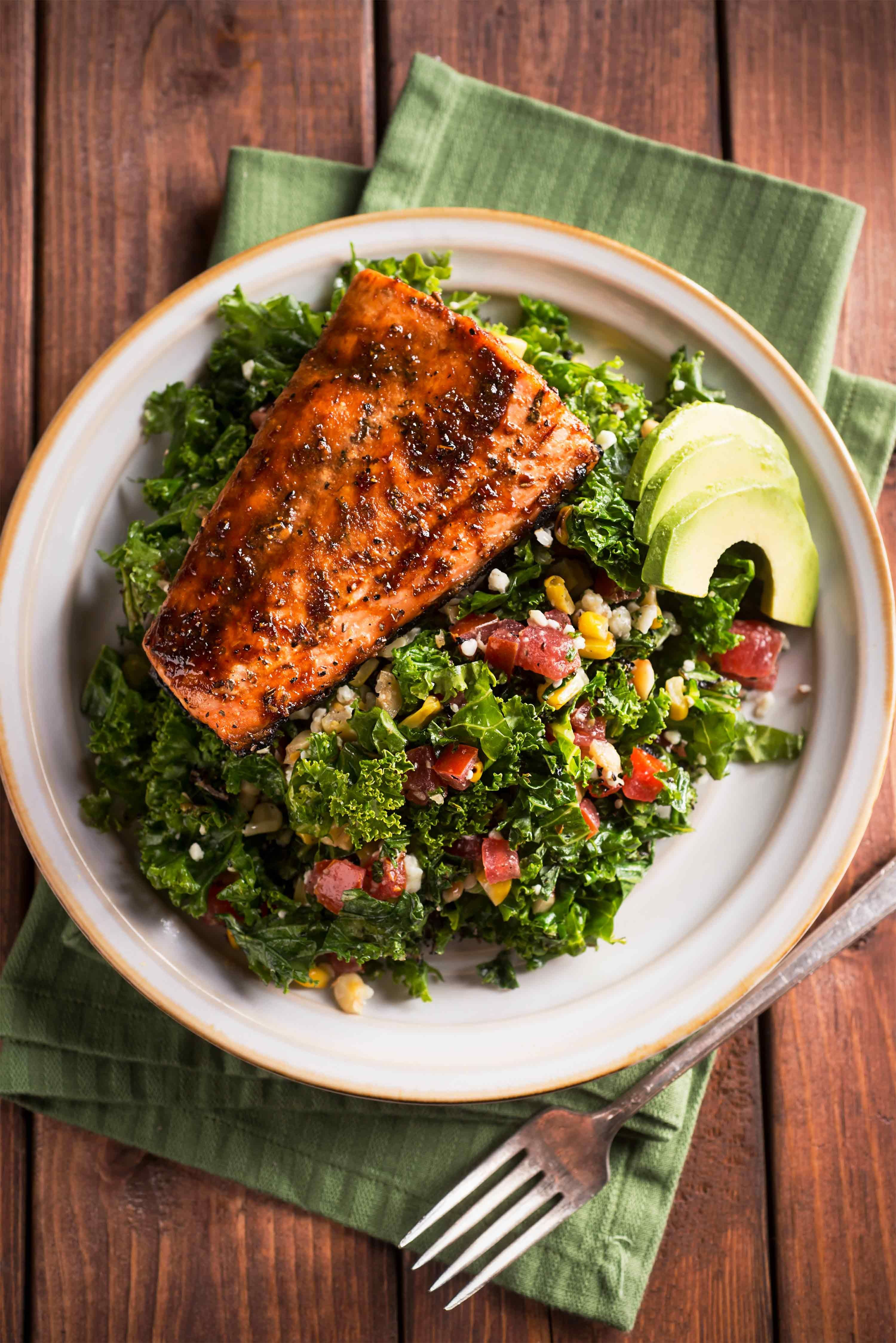 A plate of kale salad topped with grilled salmon.