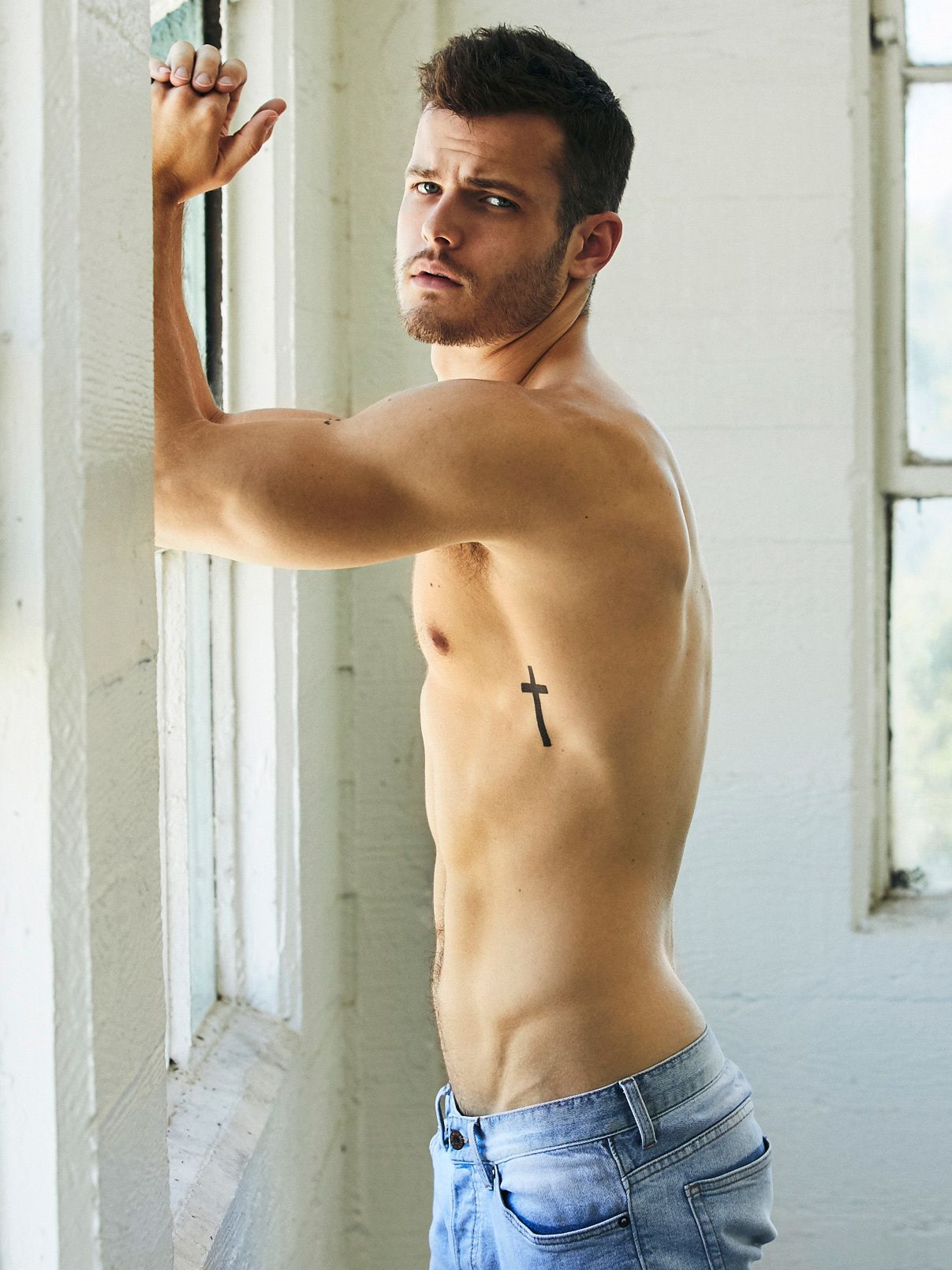 Y&R star Michael Mealor shirtless leaning against a window.