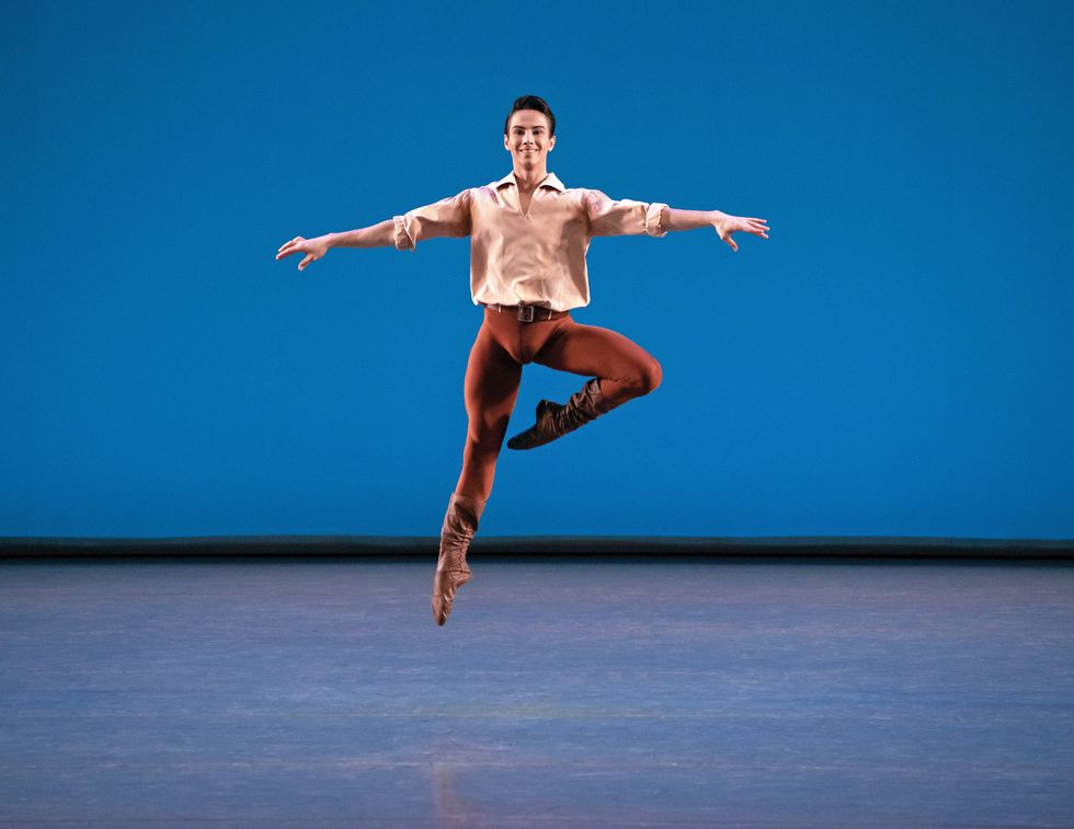 Mejia onstage in a light brown blouse and brown leggings and boots jumping in the air against a blue background. He's smiling at the audience.