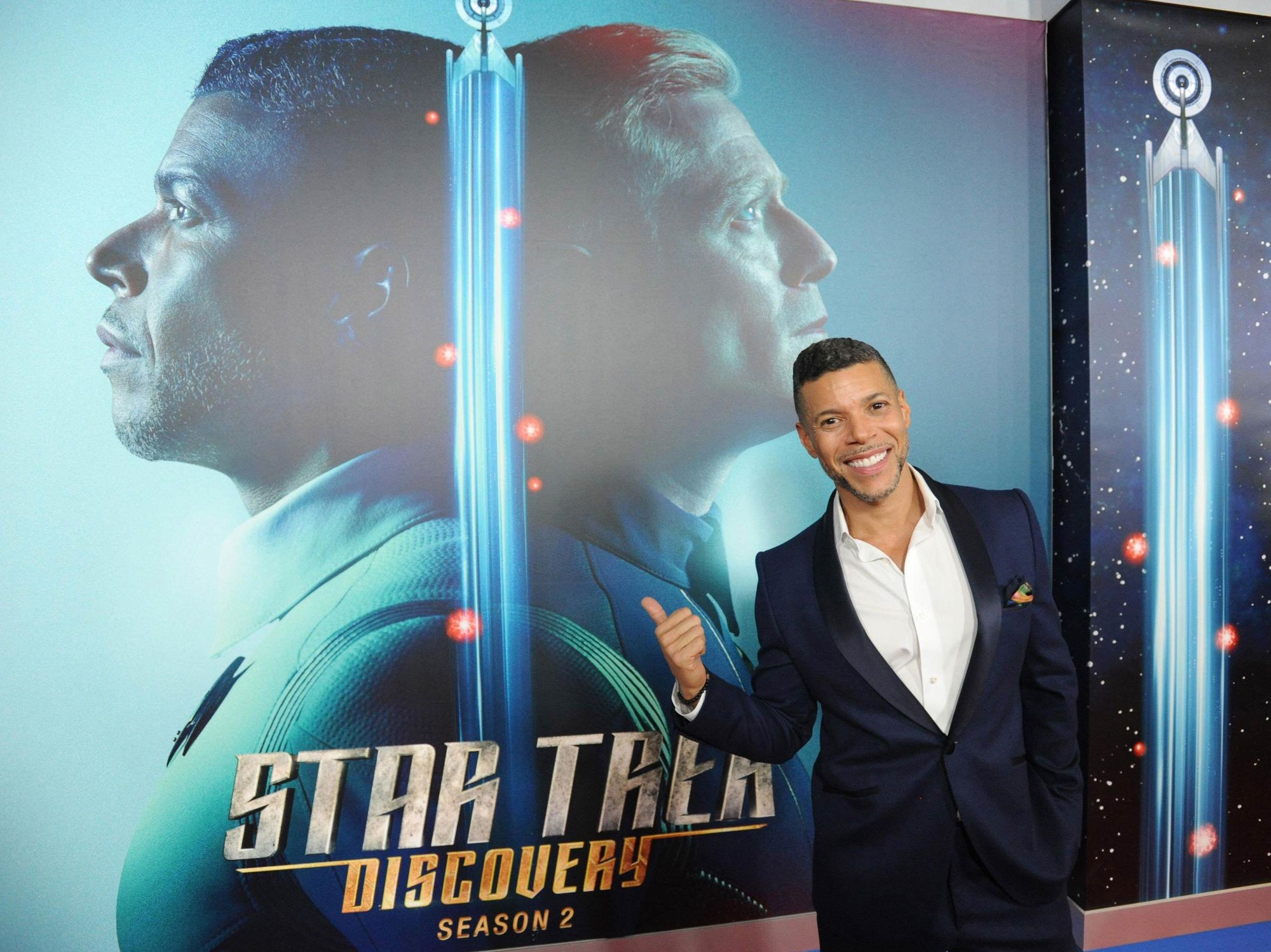 Wilson Cruz posing in front of a Star Trek: Discovery poster.