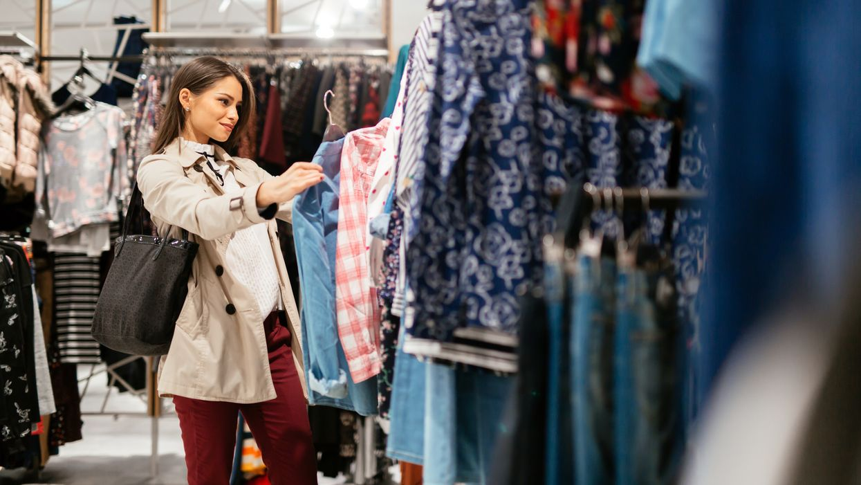 happy woman in store looking at clothes concept retail therapy shopping