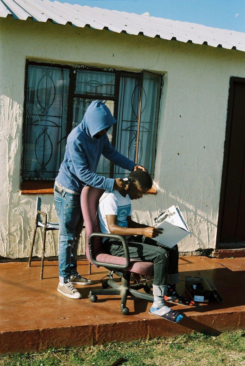 Hair-cut on the stoep in Estcourt, KwaZulu Natal in 2018. Subjects: Khehla and Lwandle Gumede.