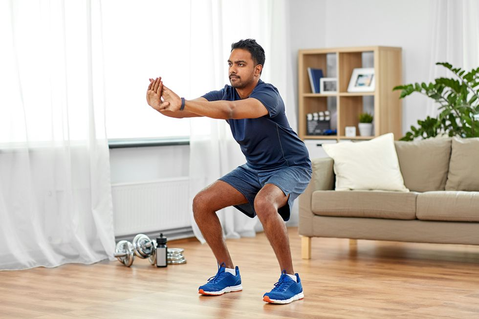 Man does squats during his home workout