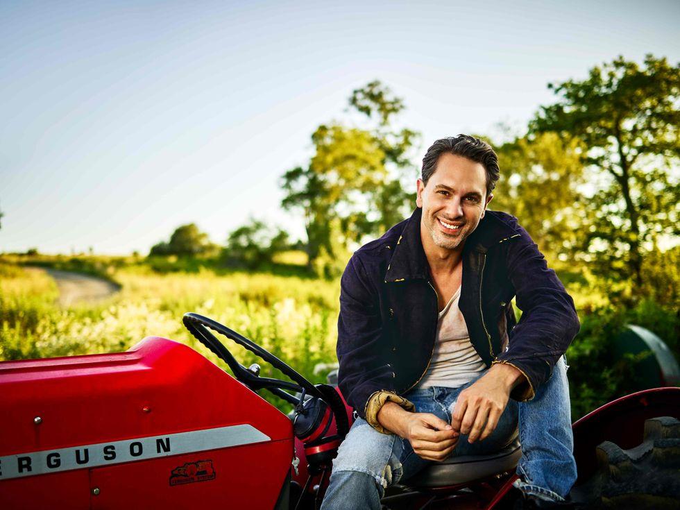 Thomas Sadoski sitting on a tractor.