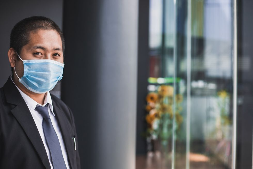 A business man wears a mask to limit the threat of coronavirus while at work.