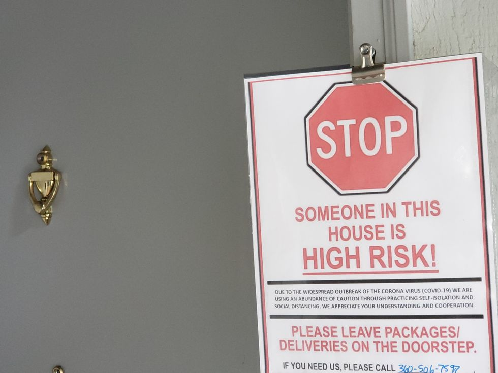 """A sign posted at a door saying """"STOP Someone in this house us HIGH RISK"""""""