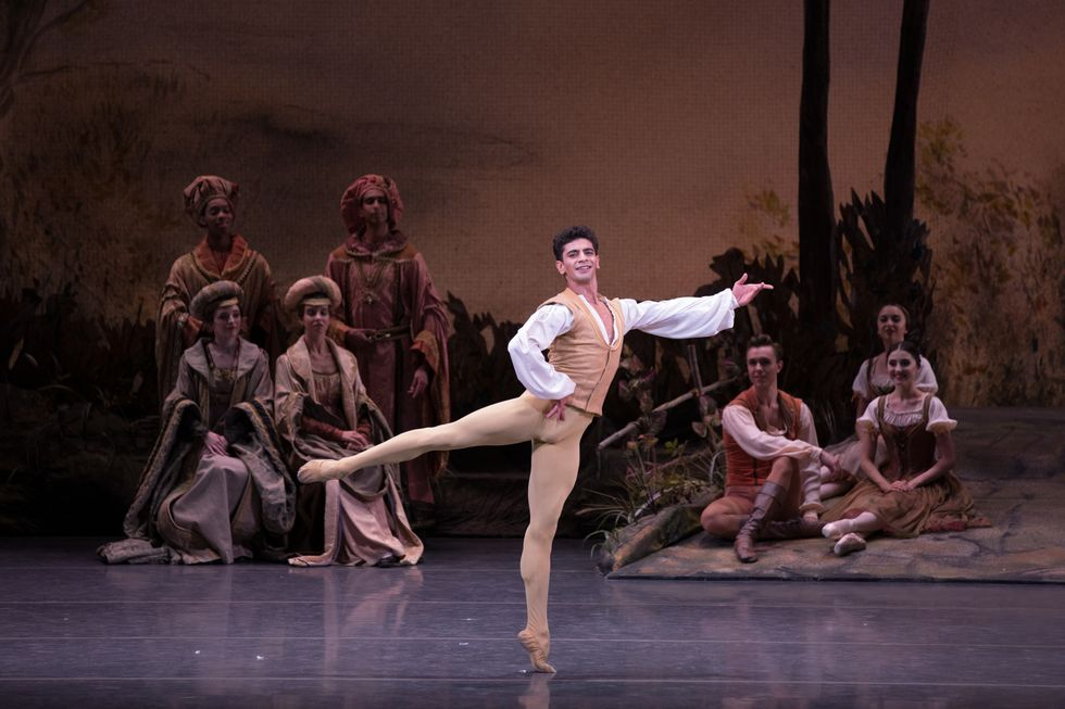 Mkrtchyan in brown tights and vest and a white blouse standing onstage in an arabesque with his hand on his hip. A group of dancers dressed as villagers and royalty sit behind him.