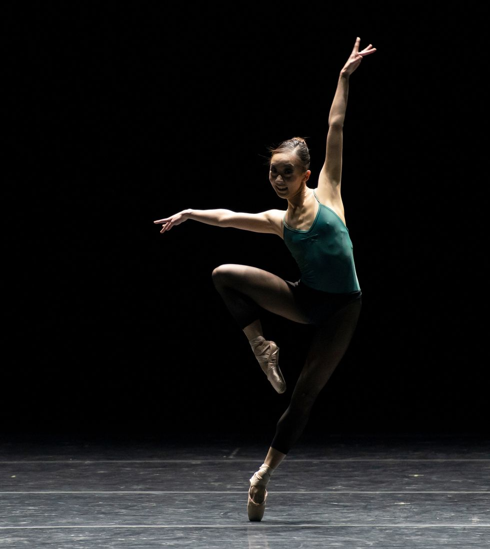 Oga, in a green leotard and black tights and pointe shoes, is onstage in an off-kilter pass\u00e9 with her arms in a jazzy extension.