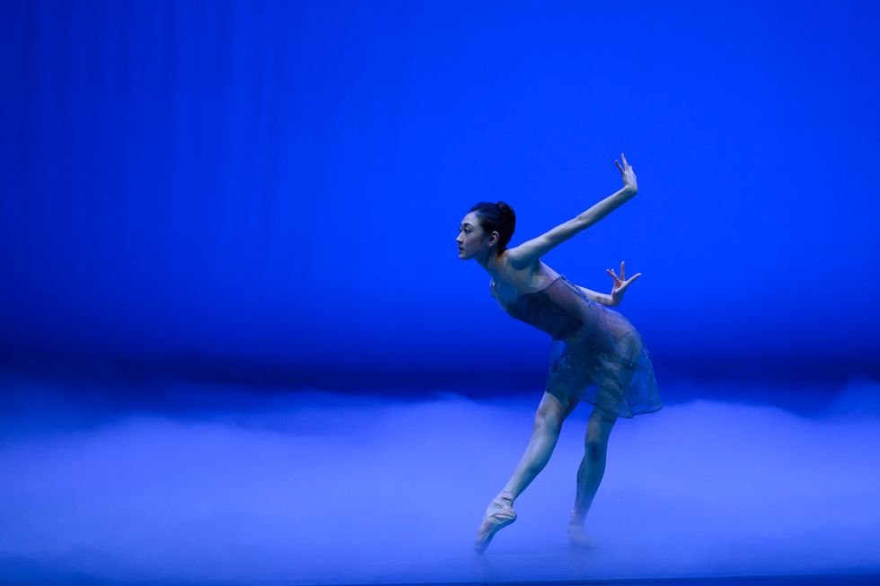 Lee, in a gauzy blue dress and pointe shoes, stands on a stage flooded with blue light and fog. One leg is extended in tendu, and she leans over with her arms behind her.