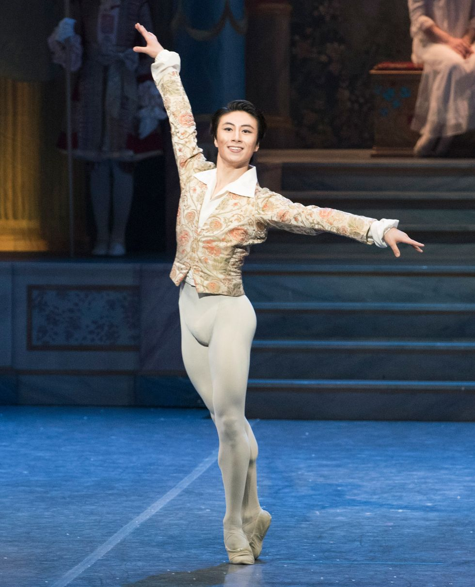 Lee stands in sous-sus onstage in white tights and a gold and white jacket, smiling at the audience.