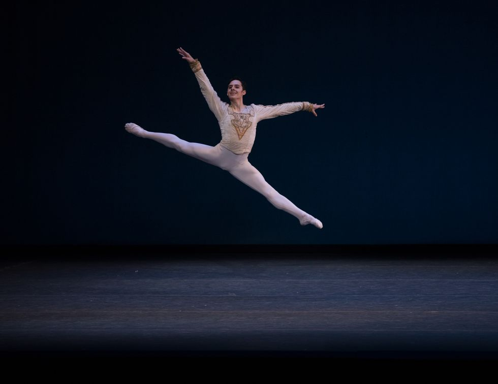 Wilkes-Davis, in white tights and a gold jacket, leaps through the air with his legs split, smiling at the audience.