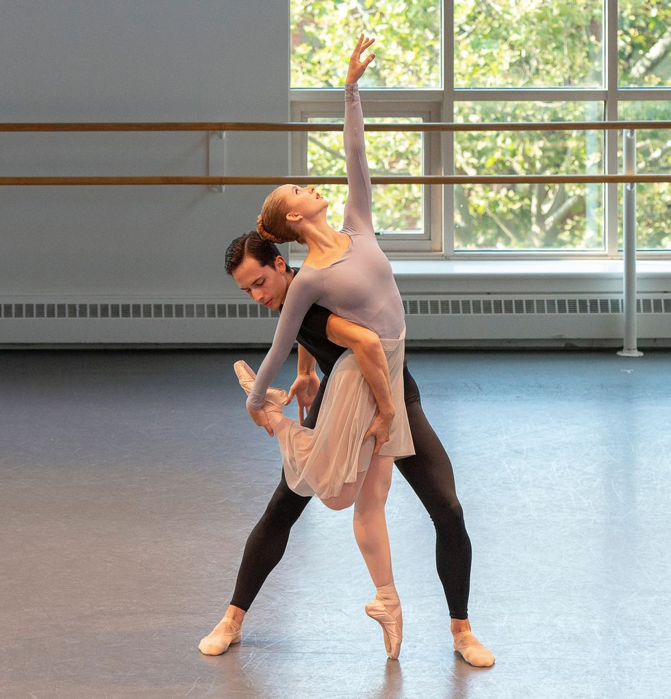 Studio shot of Novak and Wilkes-Davis in an entangled pose. Novak stands on pointe, holding one leg behind her and reaches toward the ceiling.