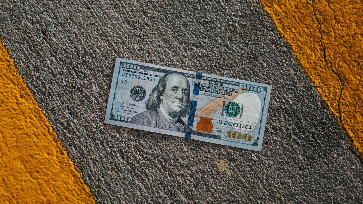 a hundred US dollar bill note on the ground