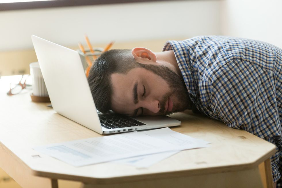 Overworked man exhausted at work