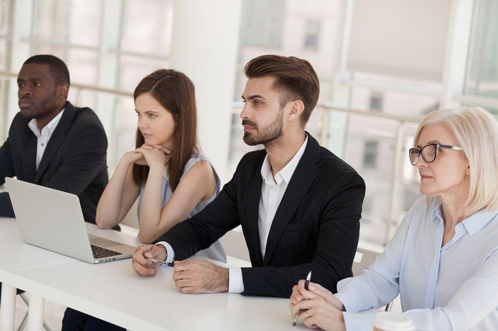 Job candidates listen during a group interview