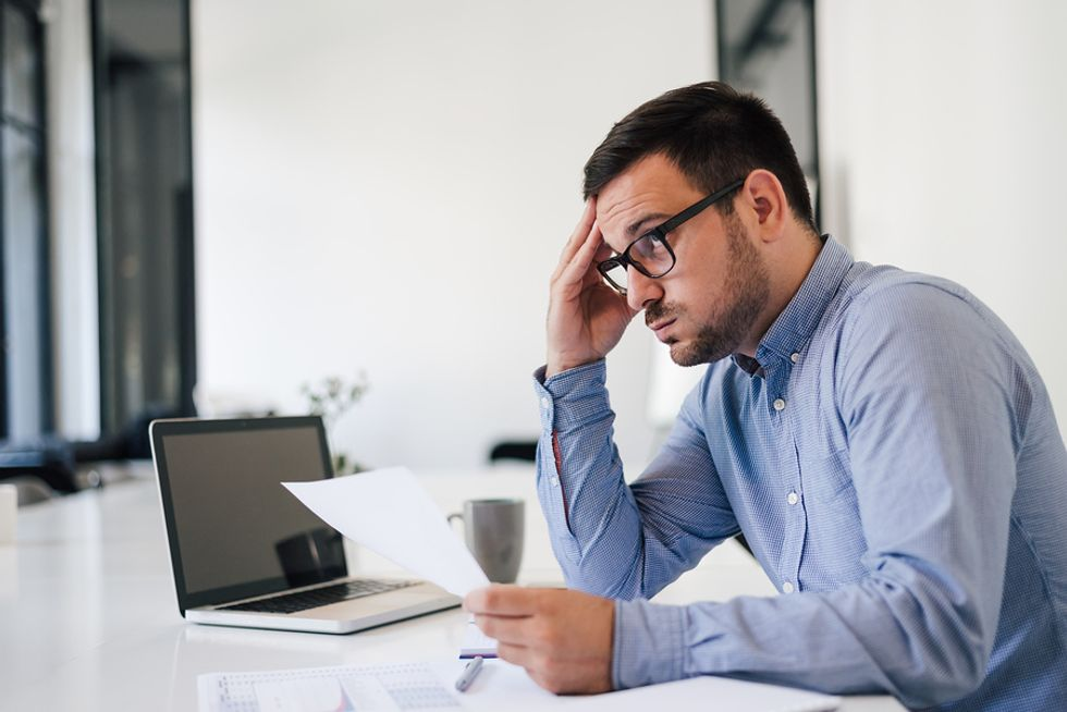 Stressed out man working at a job he took out of desperation