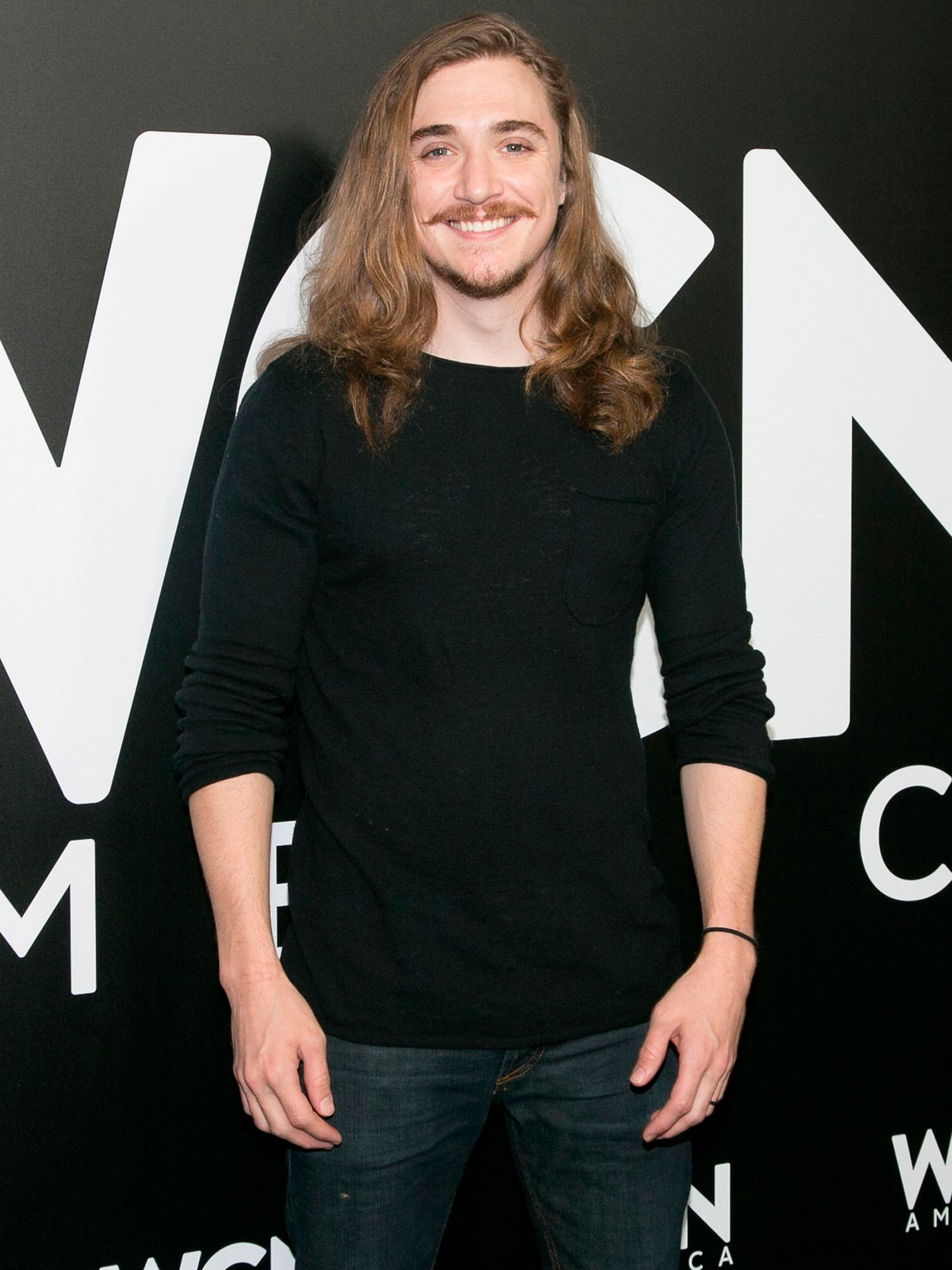 Actor Kyle Gallner in a black shirt and jeans.