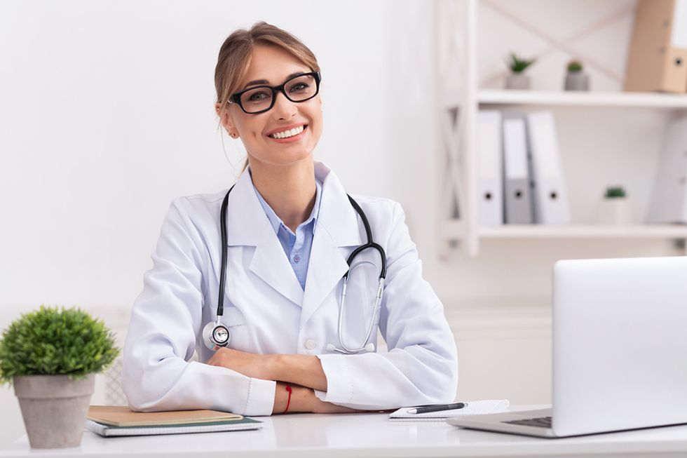 Woman doctor smiles at her desk