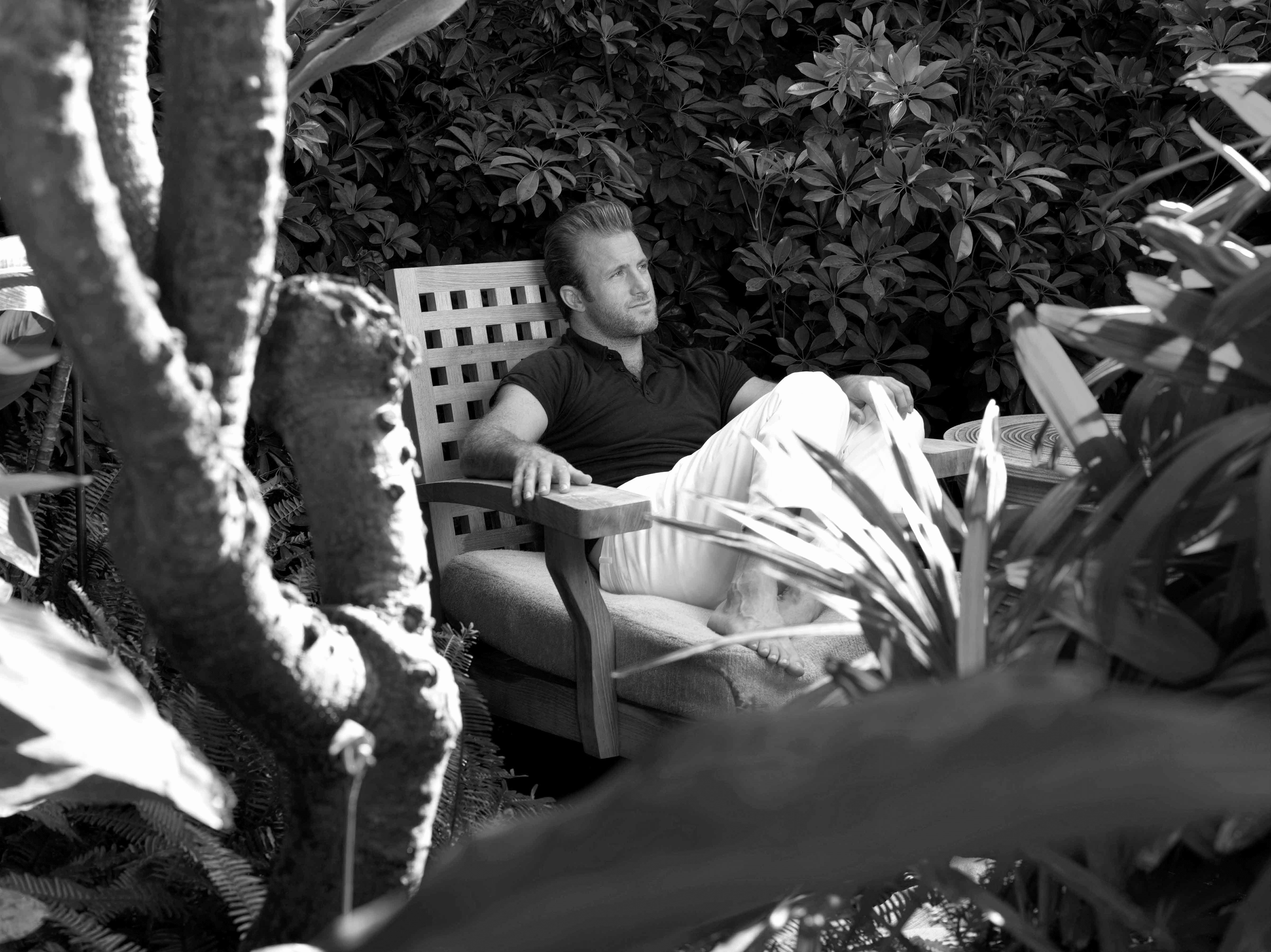 Black and white photo of Scott Caan sitting in a garden.
