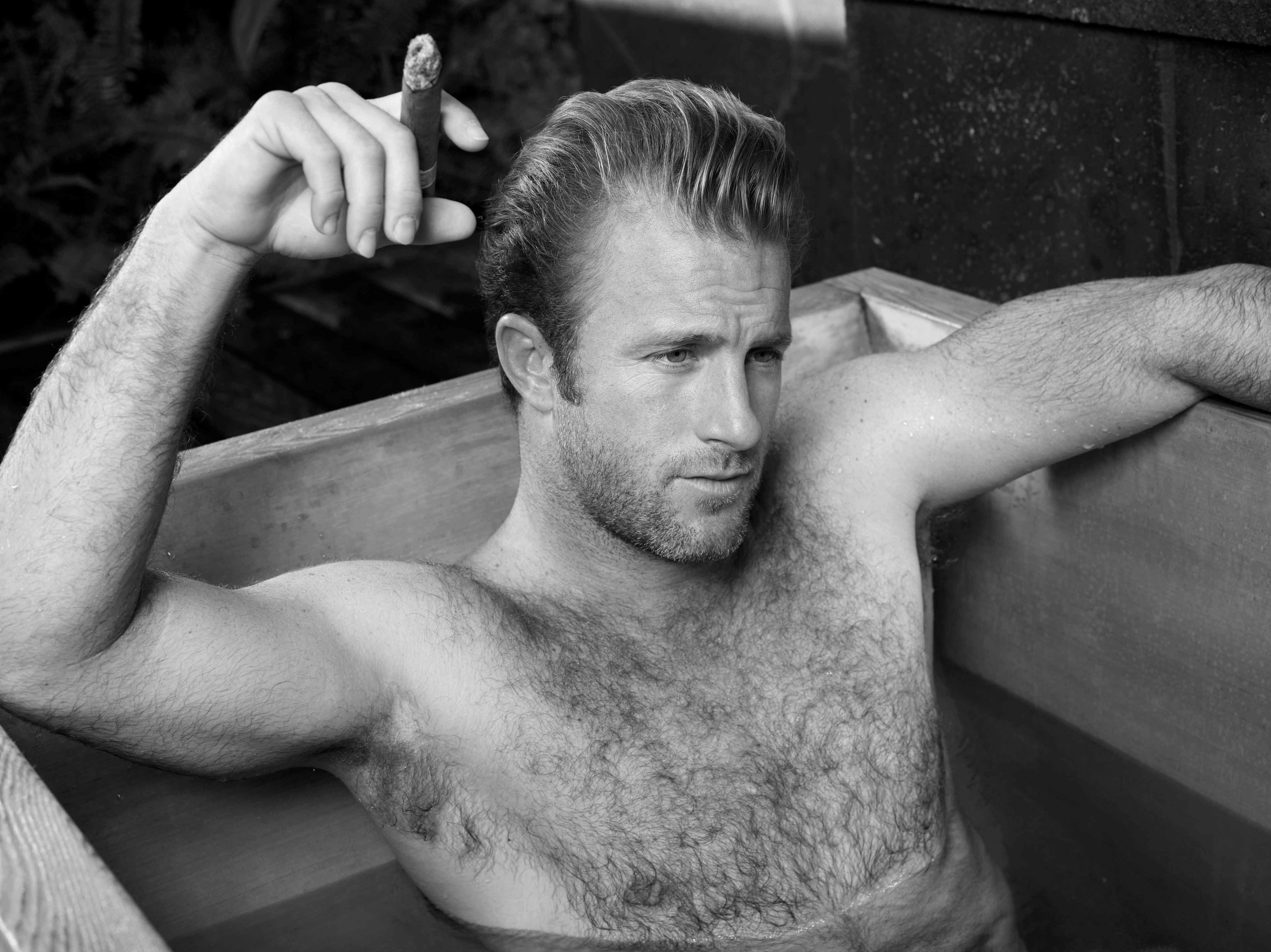 Black and white photo of Scott Caan smoking a cigar in a hot tub.