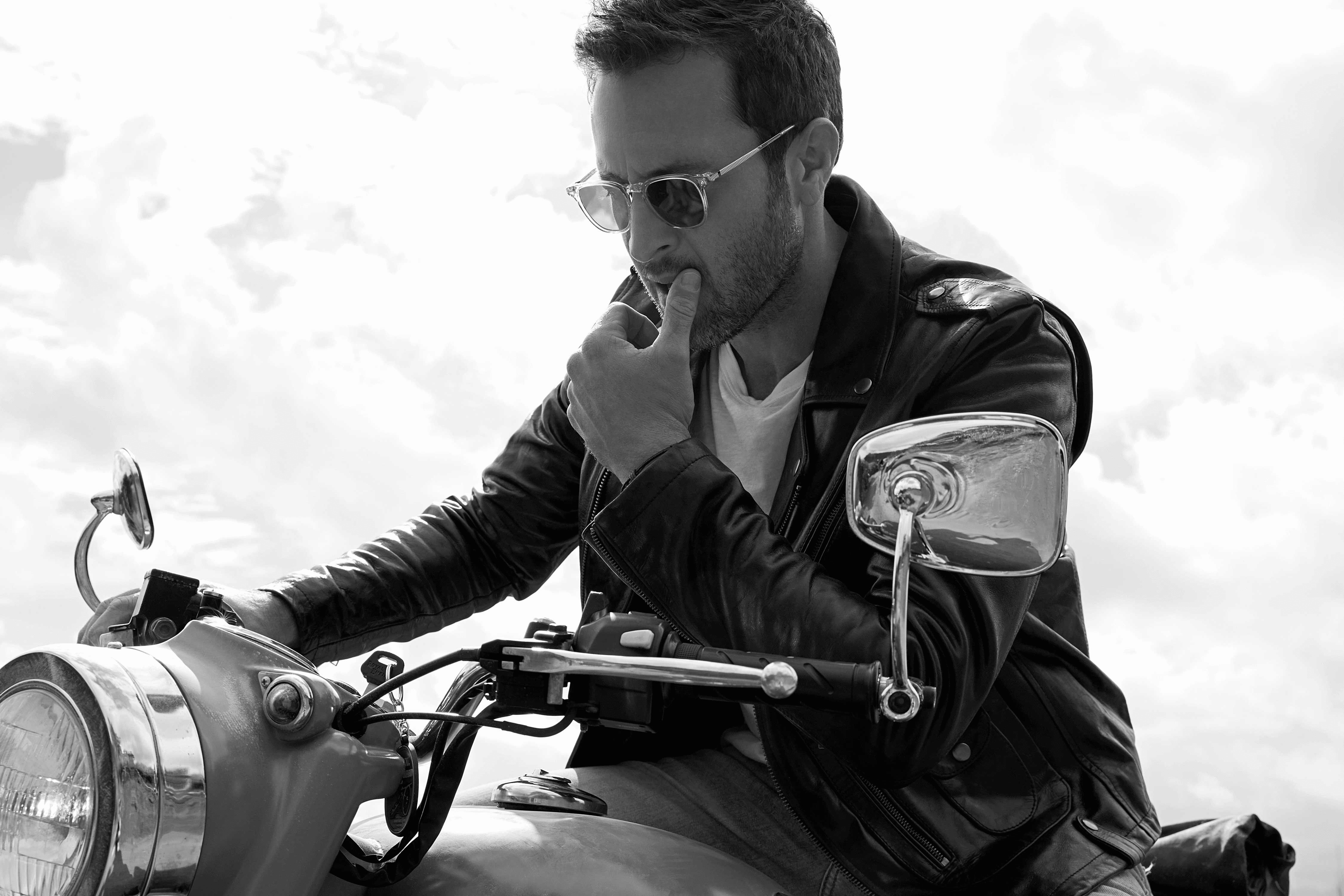 Black and white photo of Alex O'Loughlin riding a vintage motorcycle.