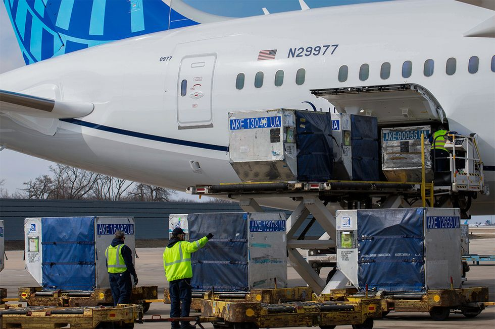 United ramp crew members help place cargo on a United flight
