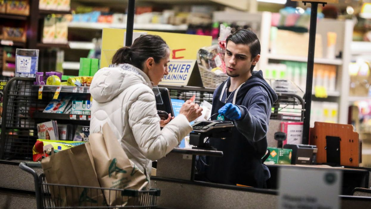 woman buying groceries at cash register