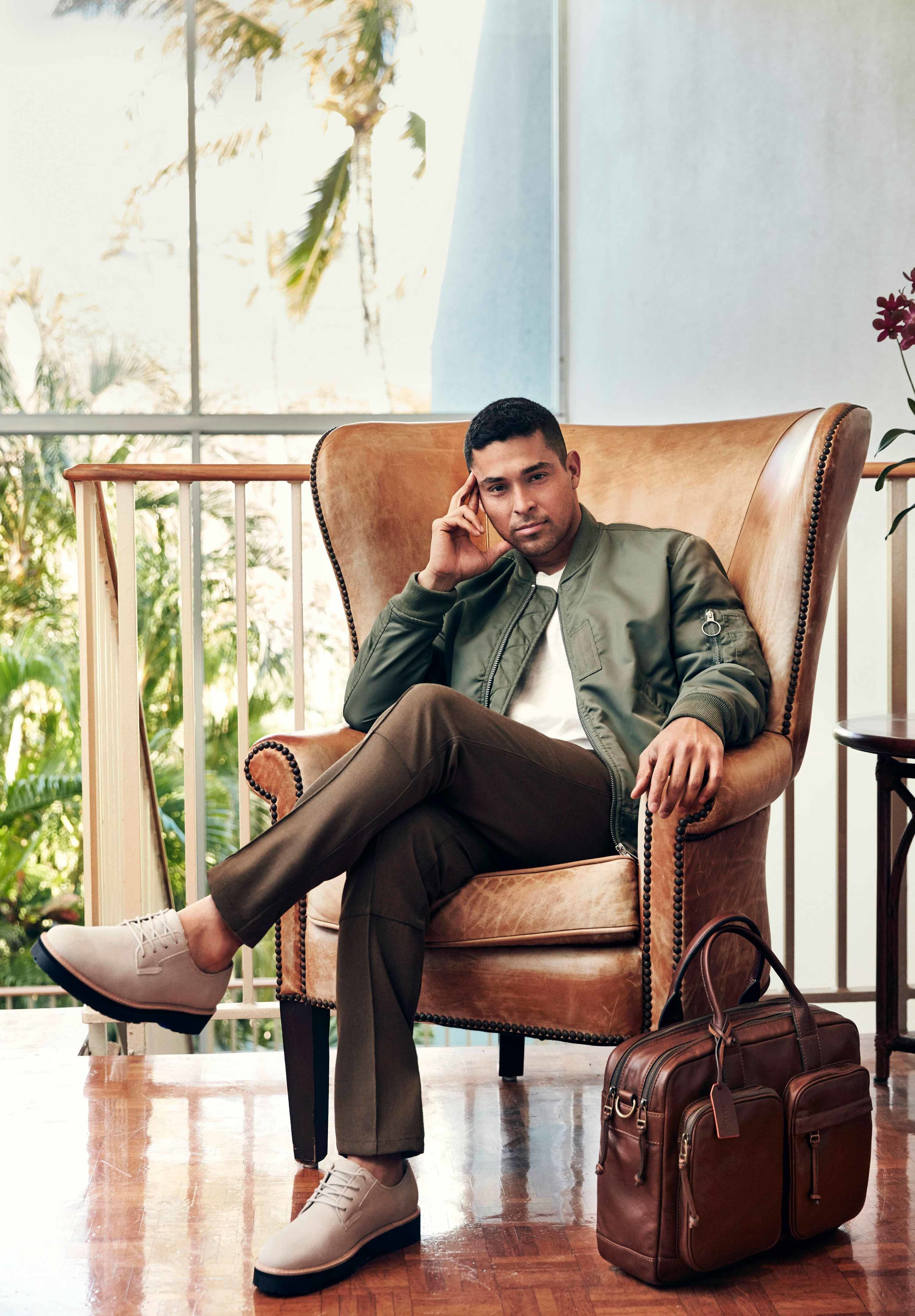 Wilmer Valderrama sitting indoors in a light brown leather chair leaning his temple on his hand