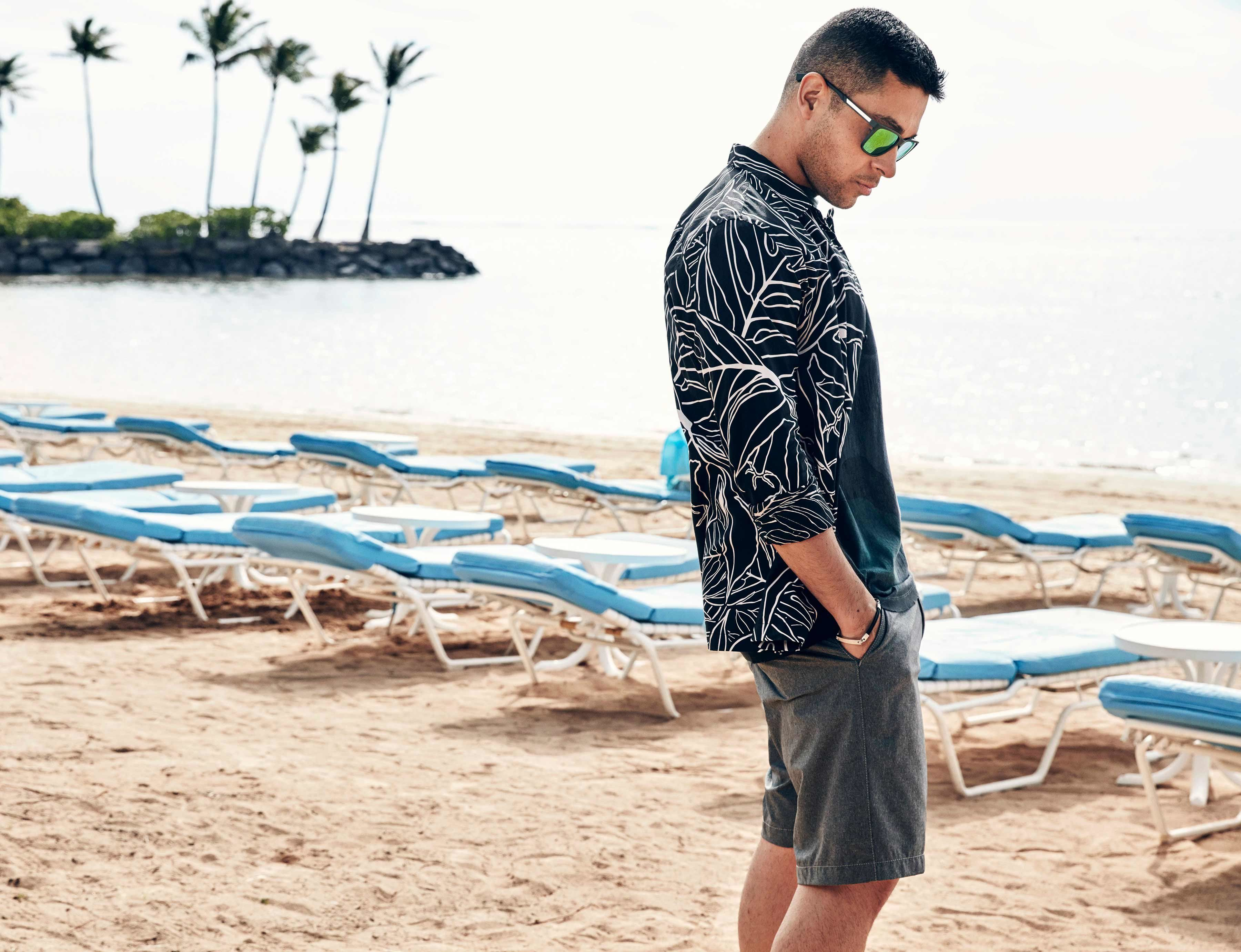 Wilmer Valderrama in a striped jacket looking down on the sandy beach in front of rows of blue lounge chairs